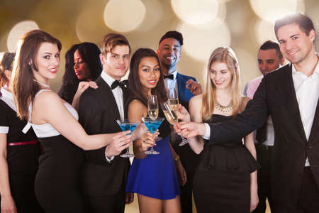 Group portrait of happy multiethnic friends toasting drinks at nightclub