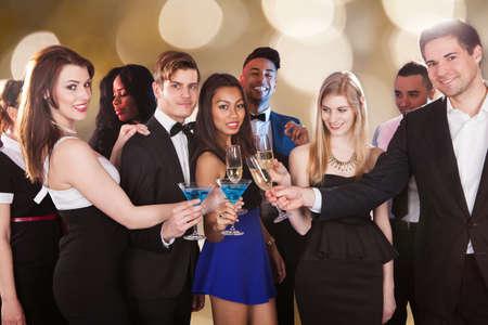 donne eleganti: Ritratto di gruppo di amici felici multietniche tostatura bevande al locale notturno