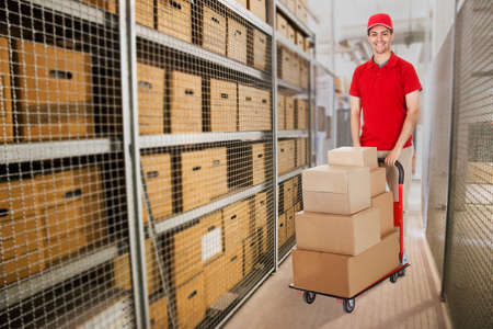 man pushing: Portrait of happy delivery man pushing cart full of cardboard boxes in warehouse Stock Photo