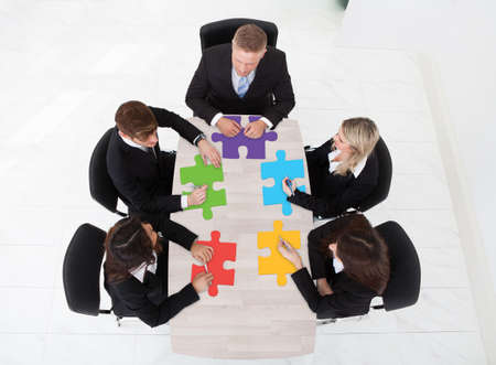 High angle view of businesspeople with jigsaw pieces sitting at table in office photo