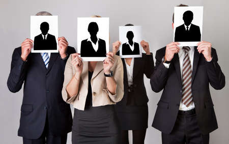 Group of businesspeople holding photographs in front of faces against gray background photo