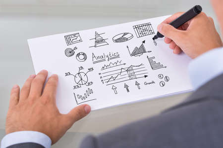 business advisor: Cropped image of businessman preparing analytical diagrams at table in office