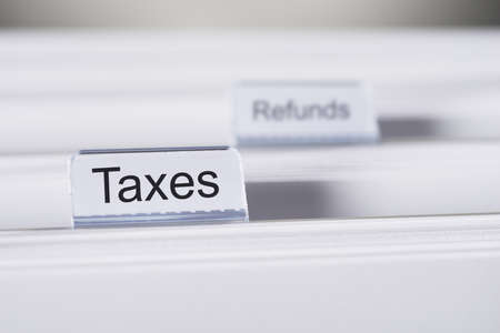 refunds: Closeup of Taxes and Refunds tabs on folders