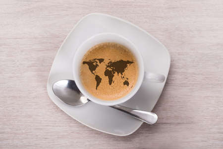 Directly above shot of coffee with world map on wooden table.  Stock Photo