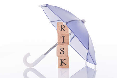 Risk wooden blocks under umbrella isolated over white background Stock Photo