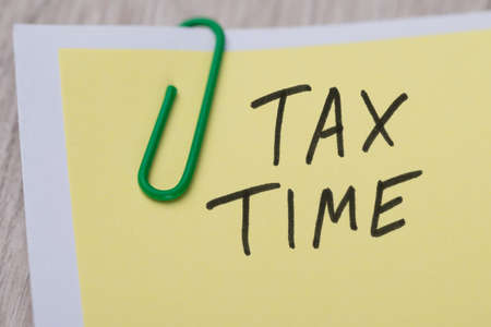 Closeup of Tax Time written on yellow paper note with paperclip photo