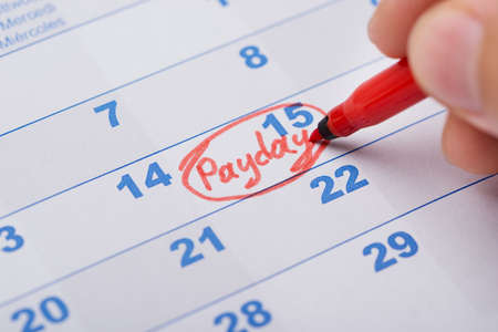 payday: Cropped image of hand marking Payday on calendar