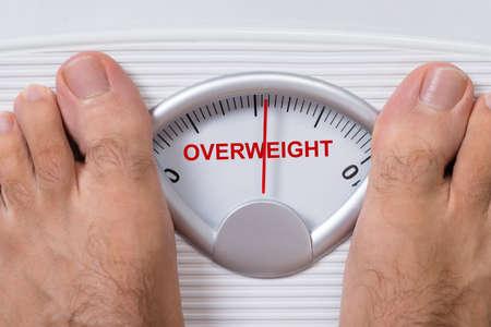 pies masculinos: Primer plano de los pies del hombre en la escala de peso que indica sobrepeso