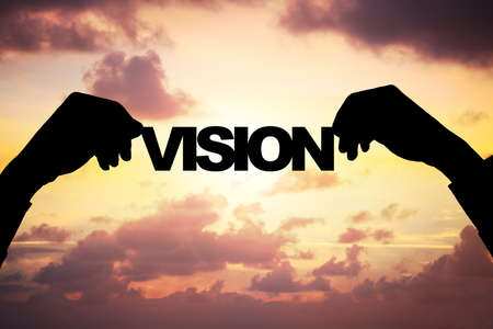 corporate vision: Cropped image of silhouette businessmans hands holding VISION word against cloudy sky during sunset Stock Photo