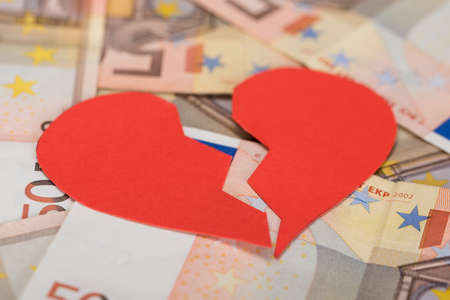 heart problems: Closeup of red broken heart on euro banknotes