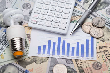 Closeup of energy saving bulb with graph and calculator on dollar bills photo