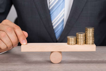 Midsection of businessman balancing coins on wooden seesaw at table