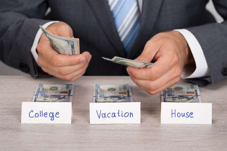 cash desk: Midsection of businessman saving cash for college; vacation and house at table