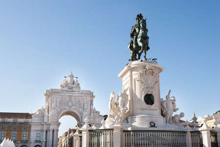 Low angle view of Statue of King Jose I and Rua Augusta Arch against clear blue sky; Lisbon; Portugal; Europe photo