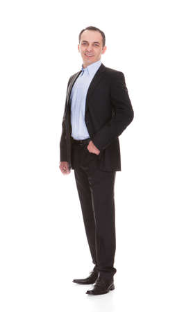 white suit: Full length portrait of happy mature businessman standing against white background Stock Photo