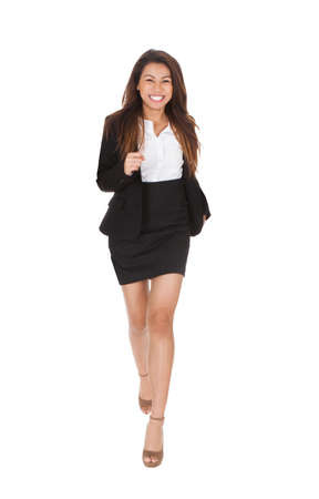 Full length portrait of happy young businesswoman running over white background