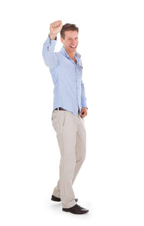 clenching fists: Full length portrait of successful man clenching fist against white background Stock Photo