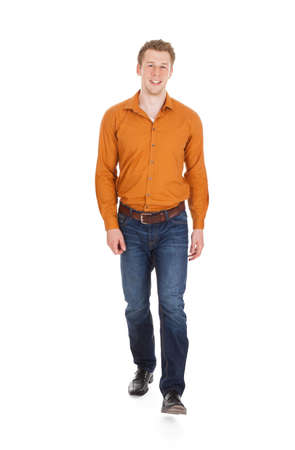 Full length portrait of handsome young man in smart casuals walking against white background
