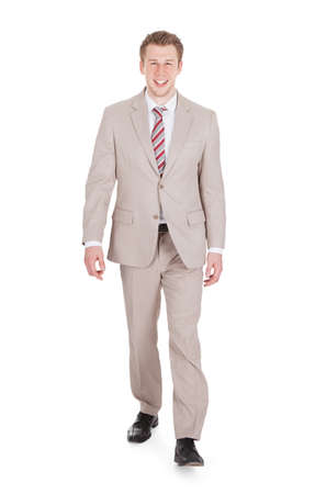 people walking white background: Full length portrait of handsome young businessman walking against white background