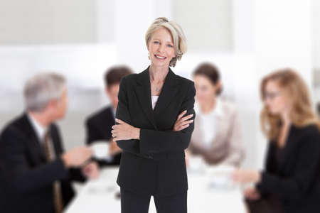Portrait of confident mature businesswoman standing arms crossed against colleagues in boardroom