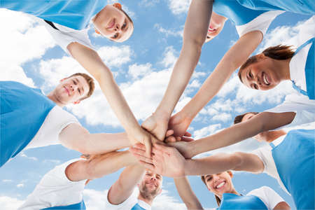 strong team: Directly below shot of diverse professional cleaners piling hands against sky Stock Photo