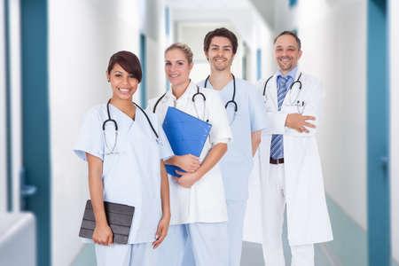 Portrait of multiethnic doctors with stethoscopes around neck standing in hospital corridor photo