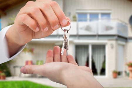 Cropped image of real estate agent giving keys to owner against new house Standard-Bild
