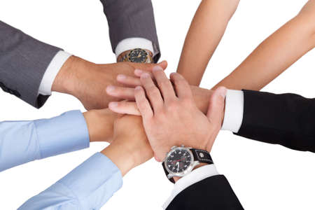 four hands: Closeup of business peoples hands on top of each other symbolizing unity against white background