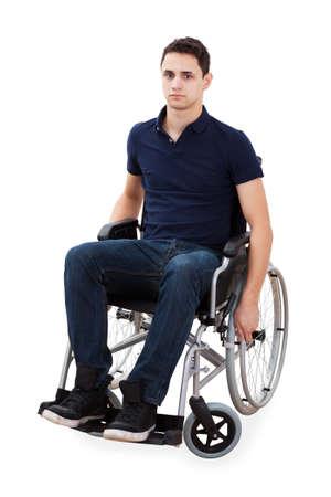 persona en silla de ruedas: Retrato de cuerpo entero del hombre joven confidente que se sienta en la silla de ruedas aisladas sobre fondo blanco