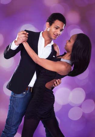 Romantic multiethnic couple dancing against purple background
