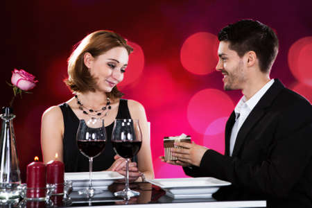 Loving man giving present to woman while having wine at restaurant table photo