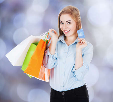 Portrait of happy businesswoman with shopping bags and credit card against colored background photo