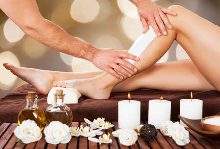 depilacion con cera: Imagen recortada de esteticista masculina depilación pierna de la mujer en el spa Foto de archivo