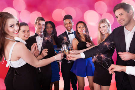 Group portrait of multiethnic friends holding sparklers while toasting drinks at nightclub