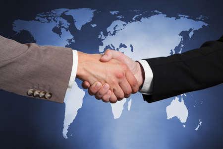 global partnership: Cropped image of businessmen shaking hands against worldmap. Stock Photo