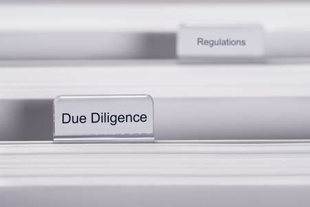 due: Closeup of folders marked with Due Diligence and Regulations