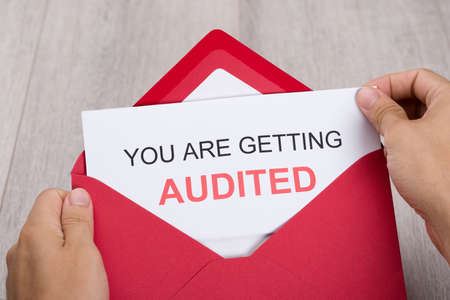 taxation: Cropped image of hand holding You Are Getting Audited card in envelope