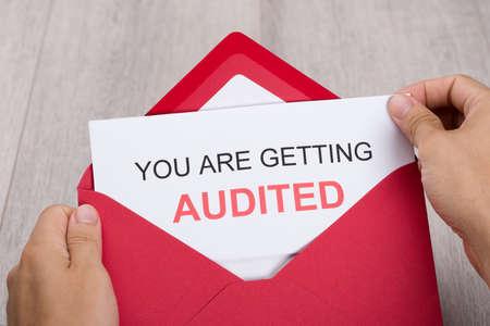 investigacion: Imagen cosechada de la mano que sostiene que está recibiendo tarjeta auditada en un sobre