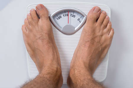 Low section of man standing on weight scale Stock Photo