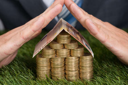 green house: Cropped image of businessman shielding house made from coins and euro note on grass Stock Photo