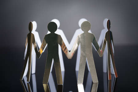 cooperative: Closeup of metal team representing unity isolated over black background