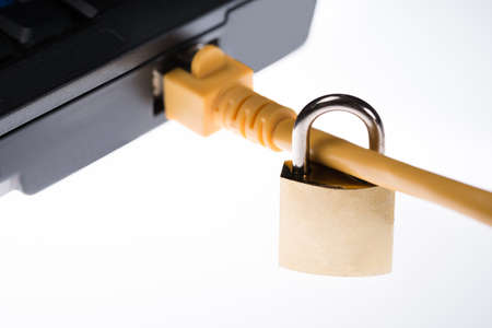 Closeup of padlock attached to plug in laptop isolated over white background photo