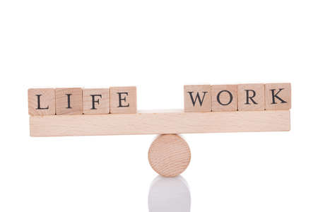 Life and Work blocks balancing on seesaw isolated over white background Stockfoto