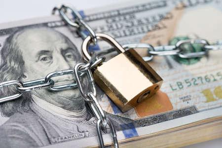 secure money: Closeup of metallic chain and padlock around dollar bundle Stock Photo