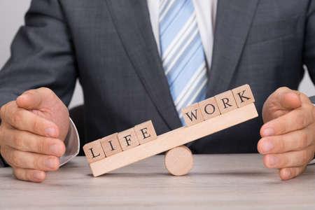 an office work: Sección media de hombre de negocios que cubre desequilibrio entre la vida y el trabajo en el balancín en la mesa