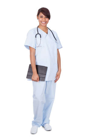 Full length portrait of female nurse holding digital tablet while standing against white background photo