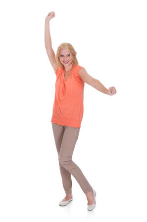clenching fists: Full length portrait of happy young woman dancing over white background