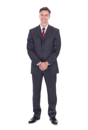 business: Full length portrait of smiling businessman with hands clasped standing against white background Stock Photo