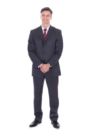 persona de pie: Retrato de cuerpo entero del hombre de negocios sonriente con las manos juntas de pie contra el fondo blanco