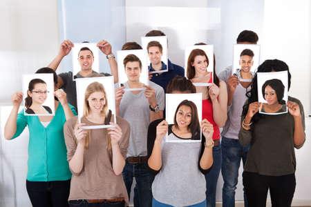 Groupe d'étudiants multiethniques détenant photos en face de visages à la salle de classe Banque d'images